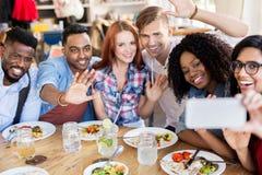 Amis mangeant et prenant le selfie au restaurant Photographie stock libre de droits