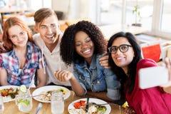 Amis mangeant et prenant le selfie au restaurant Image stock