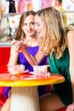 Amis mangeant la crème glacée en café Photo stock