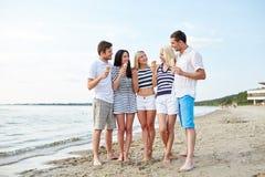 Amis mangeant la crème glacée et parlant sur la plage Photographie stock