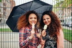 Amis mangeant la crème glacée sous la pluie Photographie stock libre de droits