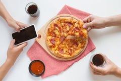 Amis mangeant la partie de pizza à la maison, plan rapproché Photographie stock libre de droits