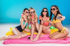 Amis mangeant la pastèque et prenant le selfie sur le smartphone sur la plage Photographie stock