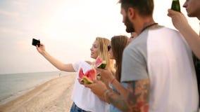 Amis mangeant la pastèque se tenant sur la plage sablonneuse et prenant des selfies avec l'appareil-photo de smartphone Port de j clips vidéos