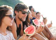Amis mangeant la pastèque sur la plage Image stock