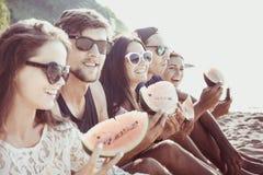 Amis mangeant la pastèque sur la plage Photographie stock libre de droits