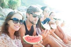 Amis mangeant la pastèque sur la plage Photos stock