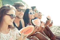 Amis mangeant la pastèque sur la plage Photo stock