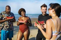 Amis mangeant la pastèque sur la plage Image libre de droits