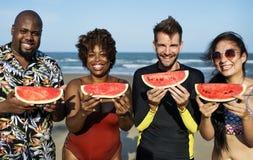 Amis mangeant la pastèque sur la plage Photographie stock