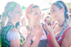 Amis mangeant la saucisse grillée chez Oktoberfest Photographie stock