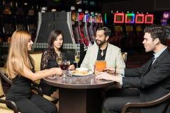 Amis mangeant le dîner dans un casino Photo stock