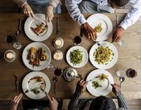 Amis mangeant le plat de cuisine de nourriture ensemble Image libre de droits