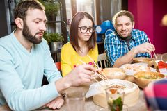 Amis mangeant les repas asiatiques au restaurant Image libre de droits