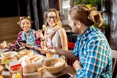Amis mangeant les repas asiatiques au restaurant Photo libre de droits