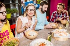 Amis mangeant les repas asiatiques au restaurant Images stock