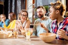 Amis mangeant les repas asiatiques au restaurant Photographie stock
