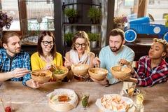 Amis mangeant les repas asiatiques au restaurant Photos libres de droits