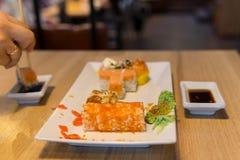 Amis mangeant les sushi et l'immersion en sauce dans le bar à sushis Image libre de droits