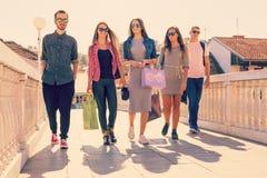 Amis marchant après l'achat dans la ville Photos libres de droits