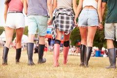Amis marchant ensemble à un site de festival de musique, vue arrière Image libre de droits