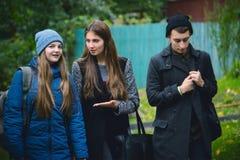 Amis marchant ensemble extérieurs en parc et parler de ville Photo stock