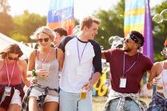 Amis marchant ensemble par un site de festival de musique Images libres de droits