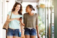 Amis marchant ensemble utilisant le téléphone portable Photos libres de droits