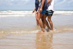 Amis marchant le long de la plage Image libre de droits