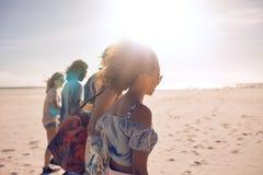 Amis marchant le long de la plage un jour ensoleillé Image libre de droits