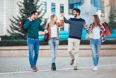 Amis marchant le long de la rue avec des paniers Photo stock