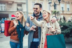 Amis marchant le long de la rue avec des paniers Photographie stock