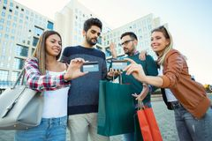 Amis marchant le long de la rue avec des paniers et des cartes de crédit Photographie stock libre de droits