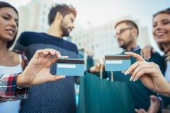 Amis marchant le long de la rue avec des paniers et des cartes de crédit Photo libre de droits