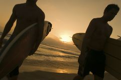 Amis marchant sur la plage au coucher du soleil Image stock