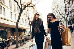 Amis marchant sur la rue de ville avec des paniers Photographie stock libre de droits