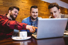 Amis masculins à l'aide de l'ordinateur portable au restaurant Photographie stock