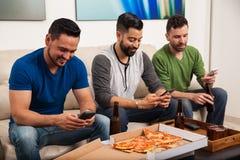 Amis masculins à l'aide des smartphones Photo libre de droits