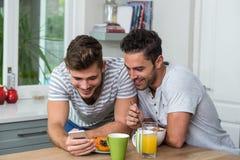 Amis masculins à l'aide du téléphone Photos stock