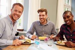 Amis masculins à la maison s'asseyant autour du Tableau pour le dîner Image stock