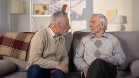 Amis masculins âgés se disputant sur le sofa à la maison, malentendu, conflit clips vidéos