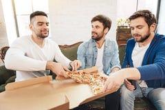 Amis masculins agréables partageant une pizza Image libre de droits
