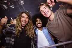 Amis masculins appréciant à la boîte de nuit pendant le festival de musique Photo libre de droits