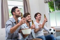 Amis masculins appréciant la bière tout en regardant le match de football à la TV Photographie stock