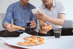 Amis masculins asiatiques appréciant sa pizza tout en se reposant sur le wat de divan Photo libre de droits