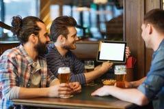 Amis masculins avec de la bière potable de PC de comprimé à la barre Images libres de droits