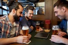 Amis masculins avec de la bière potable de PC de comprimé à la barre Image stock