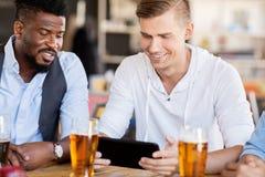 Amis masculins avec de la bière potable de PC de comprimé à la barre Photographie stock