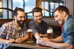 Amis masculins avec de la bière potable de smartphone à la barre Photographie stock libre de droits