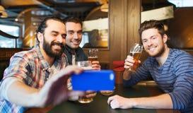 Amis masculins avec de la bière potable de smartphone à la barre Photo stock